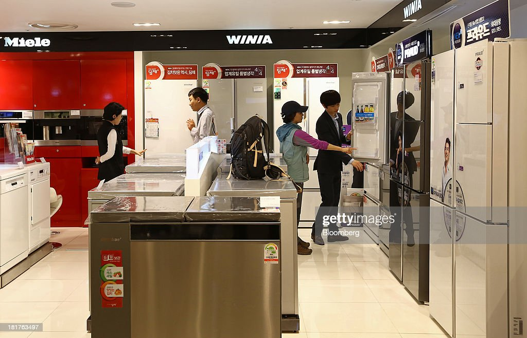 Customers browse WiniaMando Inc. refrigerators at a Shinsegae Co. department store in Seoul, South Korea, on Tuesday, Sept. 24, 2013. The South Korean economy faces headwinds, with record household debt and a sluggish housing market weighing on consumption. Photographer: SeongJoon Cho/Bloomberg via Getty Images