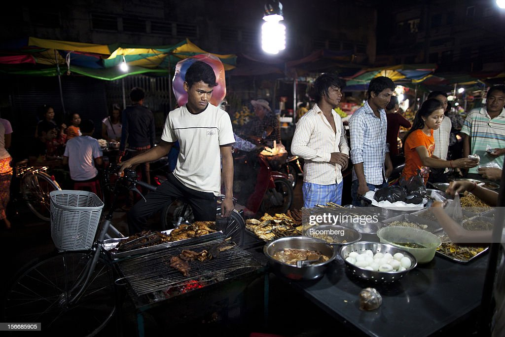 Customers buy cooked food from a stall at Kandal Market in downtown Phnom Penh, Cambodia, on Saturday, Nov. 17, 2012. U.S. President Barack Obama arrives in Phnom Penh later today to join the Association of Southeast Asian Nations (Asean) East Asia Summit, which also includes leaders from Japan, South Korea, India, Russia, Australia and New Zealand. Photographer: Will Baxter/Bloomberg via Getty Images