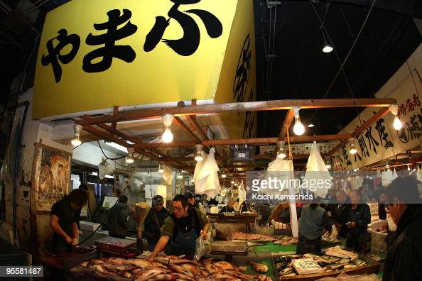 Customers buy fish on sale at a stall during the new year's first auction at the Tsukiji fish market on January 5 2010 in Tokyo Japan The market...