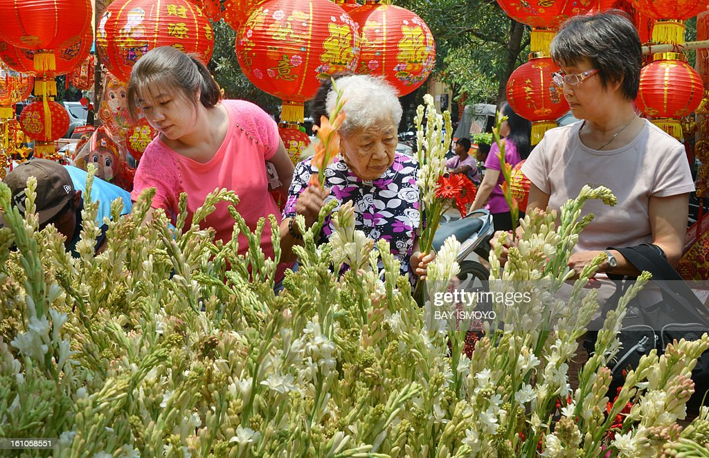 Customers buy flowers from a sidewalk vendor selling goods for the Chinese Lunar New Year in the Indonesian capital city of Jakarta on February 9, 2013 the country's minority Chinese-Indonesians prepare to celebrate the Chinese New Year. The Year of the Snake falls across the region on February 10. AFP PHOTO / Bay ISMOYO