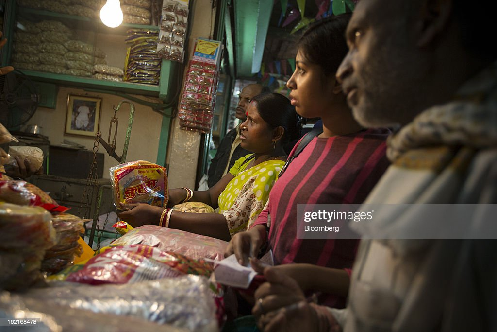 Customers buy food at a grocery store in the Burrabazar area of Kolkata, India, on Tuesday, Feb. 19, 2013. India's slowest economic expansion in a decade is limiting profit growth at the biggest companies even as foreigners remain net buyers of the nation's stocks, according to Kotak Institutional Equities. Photographer: Brent Lewin/Bloomberg via Getty Images