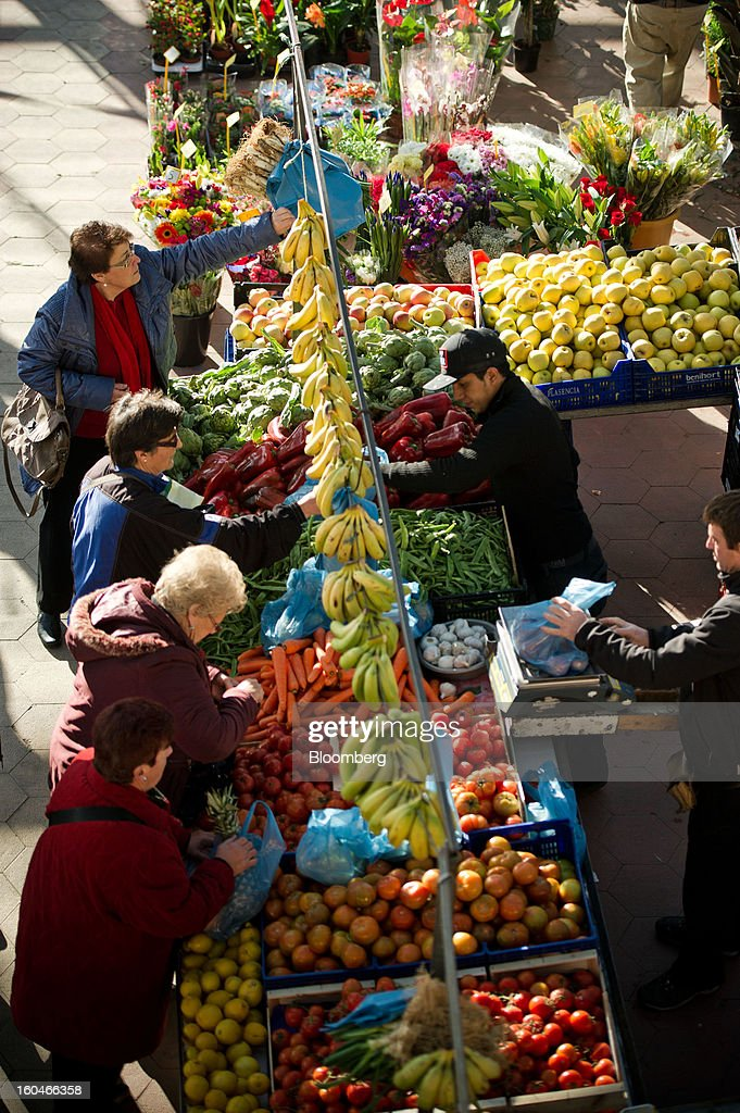 Customers buy fruit and vegetable from a stall in the weekly market in Figueres, Spain, on Thursday, Jan. 31, 2013. Spain's recession deepened more than economists forecast in the fourth quarter as the government's struggle to rein in the euro region's second-largest budget deficit weighed on domestic demand. Photographer: David Ramos/Bloomberg via Getty Images