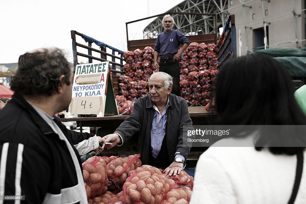 Customers buy sacks of potatoes at a farmers' market in Thessaloniki, Greece, on Saturday, Nov. 16, 2013. Greek Prime Minister Antonis Samaras, who survived a no-confidence vote on Nov. 11 with his parliamentary majority reduced to four, is trumpeting the first economic growth in seven years for 2014. Photographer: Konstantinos Tsakalidis/Bloomberg via Getty Images