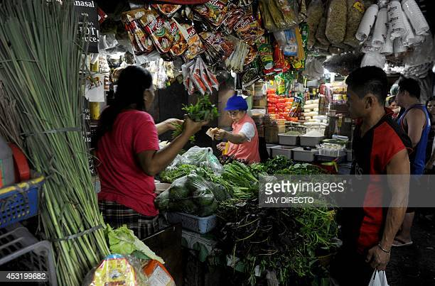 Customers buy vegetables at a market in Manila on August 5 2014 Philippine inflation shot up to a nearly threeyear high of 49 percent in July the...