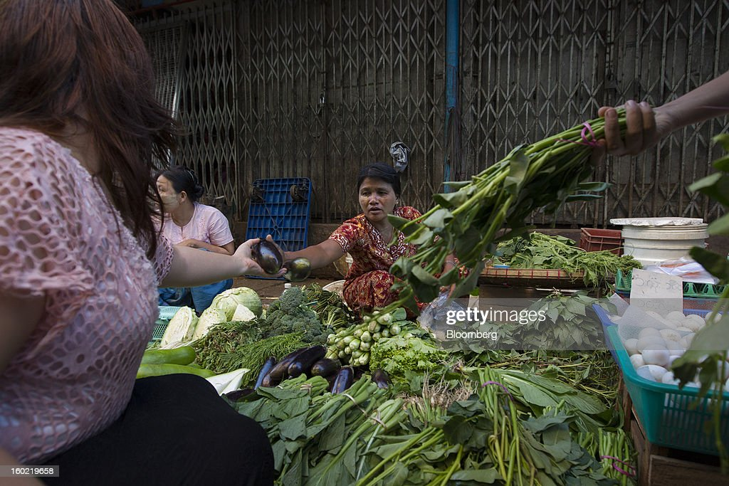 Customers buy vegetables at a market stall in Yangon, Myanmar, on Tuesday, Jan. 22, 2013. Myanmar cleared about $1 billion in overdue debt with the Asian Development Bank and World Bank using a bridge loan from Japan, opening the door for increased lending as the country seeks to overhaul its infrastructure. Photographer: Brent Lewin/Bloomberg via Getty Images