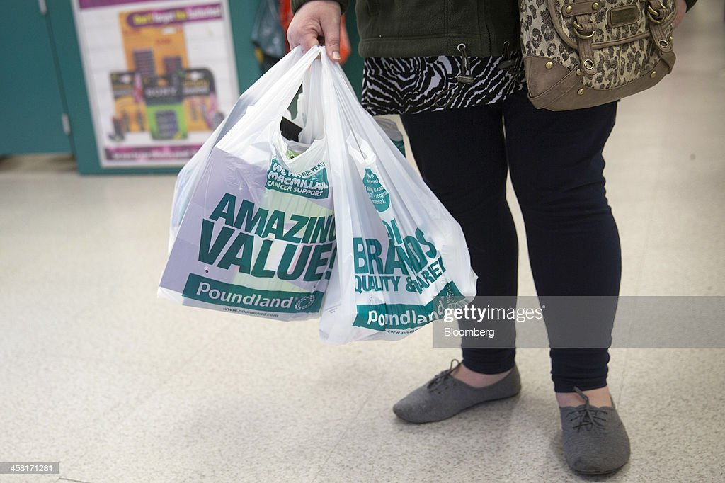 A customers carries her goods in branded plastic shopping bags as she leaves a Poundland discount store, operated by Poundland Holdings Ltd.,in Birmingham, U.K., on Friday, Dec. 20, 2013. U.K. discount retailer Poundland has hired Rothschild to manage its IPO, according to the Sunday Times newspaper. Photographer: Simon Dawson/Bloomberg via Getty Images