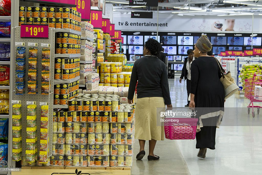 Customers carry a shopping basket past a display of canned foods inside a Game supermarket, part of Massmart Holdings Ltd., in the Fourways district of Johannesburg, South Africa, on Thursday, Aug. 22, 2013. Massmart Holdings Ltd., the South African food and goods wholesaler owned by Wal-Mart Stores Inc., said revenue growth continued to slow in August after a downturn in consumer spending hurt first-half earnings. Photographer: Nadine Hutton/Bloomberg via Getty Images