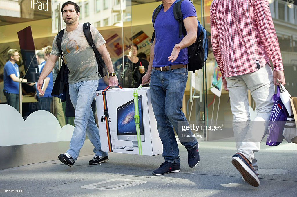 Customers carry an Apple Inc. iMac computer in front of an Apple Inc. store in San Francisco, California, U.S., on Friday, April 19, 2013. Apple Inc. is expected to release earnings data on April 23. Photographer: David Paul Morris/Bloomberg via Getty Images