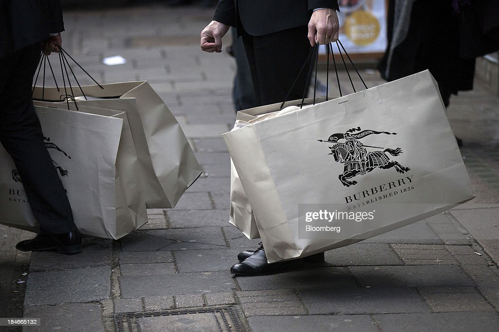 Customers carry goods in Burberry-branded shopping bags as they leave the company's store on Regent Street in London, U.K., on Wednesday, Nov. 7, 2012. Burberry Group said Christopher Bailey will become chief executive officer of the largest British luxury-goods producer, as CEO Angela Ahrendts departs the company to work at Apple Inc. Photographer: Simon Dawson/Bloomberg via Getty Images