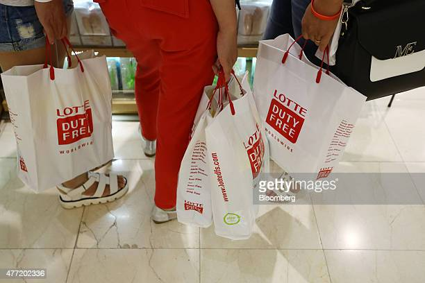 Customers carry Hotel Lotte Co Duty Free branded shopping bags at the company's store in Seoul South Korea on Monday June 15 2015 As Korean shoppers...