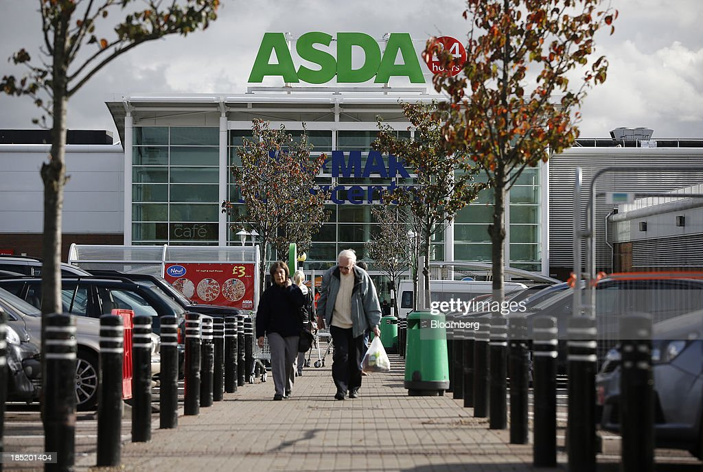 Customers carry plastic shopping bags as they leave an Asda supermarket, the U.K. retail arm of Wal-Mart Stores Inc., in Watford, U.K., on Thursday, Oct. 17, 2013. U.K. retail sales rose more than economists forecast in September as an increase in furniture demand led a rebound from a slump the previous month. Photographer: Simon Dawson/Bloomberg via Getty Images