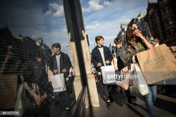 Customers carry shopping bags from Topman operated by Arcadia Group Ltd and Primark Stores Ltd fashion stores as they walk along Oxford Street in...