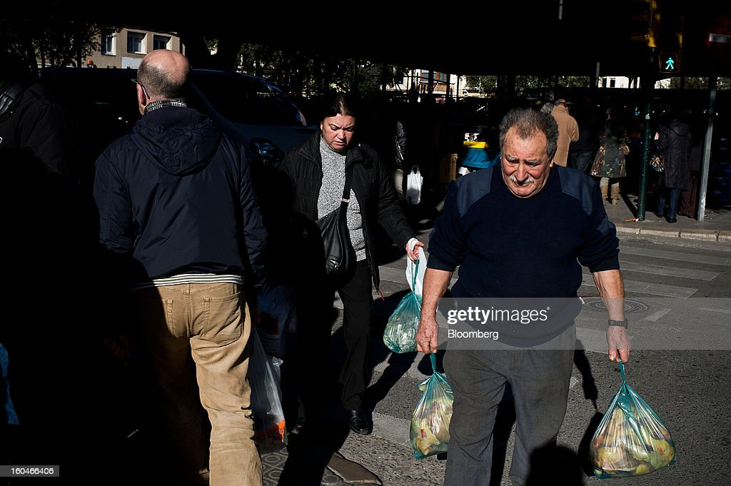 Customers carry shopping bags of fresh fruit and vegetables purchased at the weekly market in Figueres, Spain, on Thursday, Jan. 31, 2013. Spain's recession deepened more than economists forecast in the fourth quarter as the government's struggle to rein in the euro region's second-largest budget deficit weighed on domestic demand. Photographer: David Ramos/Bloomberg via Getty Images