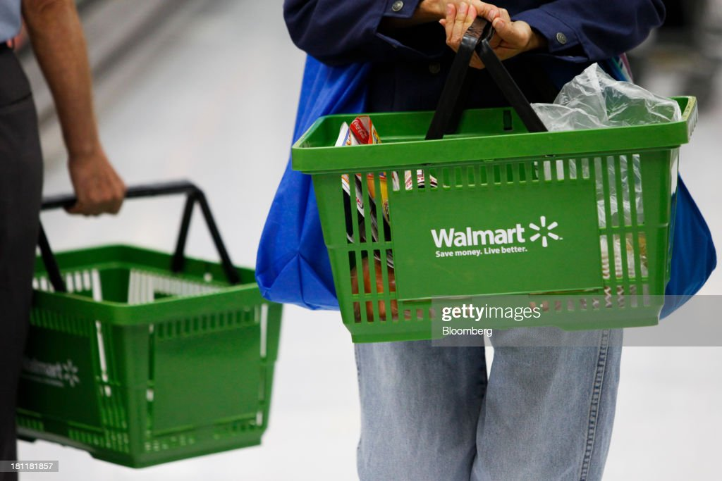 Customers carry shopping baskets during the grand opening of a Wal-Mart Stores Inc. location in the Chinatown neighborhood of Los Angeles, California, U.S., on Thursday, Sept. 19, 2013. Wal-Mart Stores Inc. will phase out 10 chemicals it sells in favor of safer alternatives and disclose the chemicals contained in four product categories, the company announced Sept. 12. Photographer: Patrick T. Fallon/Bloomberg via Getty Images