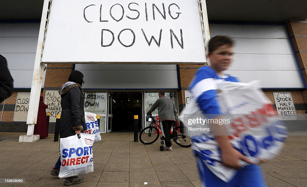 Customers carry Sports Direct International Plc branded shopping bags as they leave a JJB Sports Plc store during a closing down sale in Rochdale, U.K., on Saturday, Oct. 6, 2012. JJB Sports Plc, a U.K. sporting goods retailer, will close most of its stores with the remaining 20 being acquired by competitor Sports Direct International Plc, according to a statement from KPMG LLP, which was appointed as administrator to the Wigan, England-based company. Photographer: Paul Thomas/Bloomberg via Getty Images