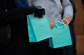 Customers carry Tiffany Co shopping bags outside the company's flagship store in New York US on Tuesday March 18 2014 Tiffany Co is expected to...