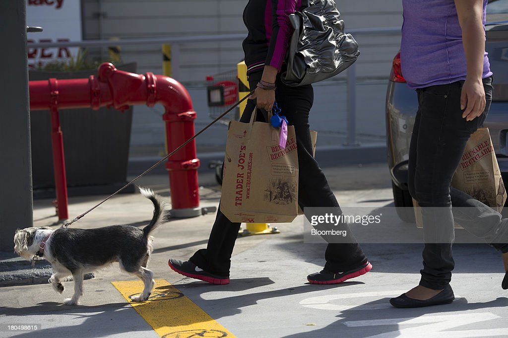 Customers carry Trader Joe's Co. shopping bags in San Francisco, California, U.S., on Friday, Sept. 13, 2013. Trader Joe's Co., the closely held grocery store chain, will end health benefits for part-time workers next year, directing them instead to anew insurance marketplaces as companies revamp medical coverage to fit the U.S. Affordable Care Act. Photographer: David Paul Morris/Bloomberg via Getty Images