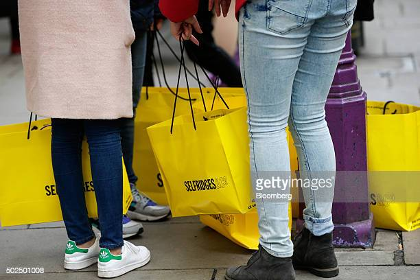 Customers carrying Selfridges Plc department store bags stand on Oxford Street in London UK on Saturday Dec 26 2015 UK retail sales volumes increased...