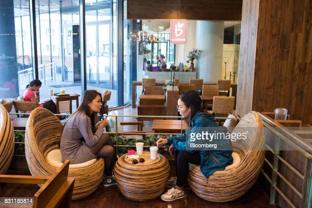 Customers chat over cups of coffee at a Caffebene Co store in Ulaanbaatar Mongolia on Saturday Aug 12 2017 The Mongolian economy is forecast by the...