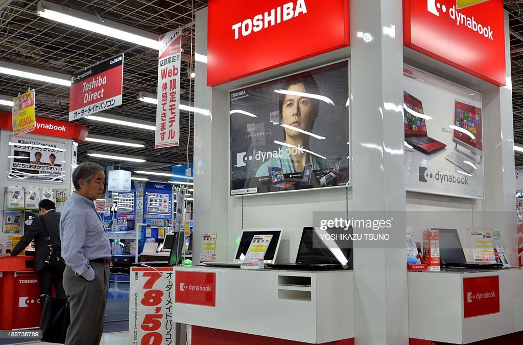 Customers check Japanese electronics giant Toshiba's notebook computers at an electric shop in Tokyo on May 8, 2014. Toshiba said its full-year net profit fell about 34 percent with one-off costs weighing on its bottom line as the Japanese firm reportedly eyes French giant Alstom's power-grid business. The fall in Toshiba's net earnings to 50.83 billion yen (500 million USD) in the fiscal year to March was chiefly due to the cost of exiting an optical disc drive business jointly run with South Korea's Samsung. AFP PHOTO / Yoshikazu TSUNO