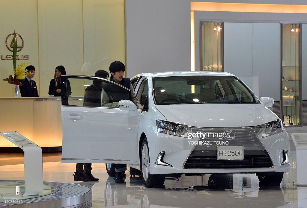 Customers check look at Toyota Motor vehicles at the company's showroom in Tokyo on February 5, 2013. Toyota said its net profit quadrupled for the nine months to December as the Japanese auto giant revised upward its full-year profit and sales forecast. AFP PHOTO / Yoshikazu TSUNO
