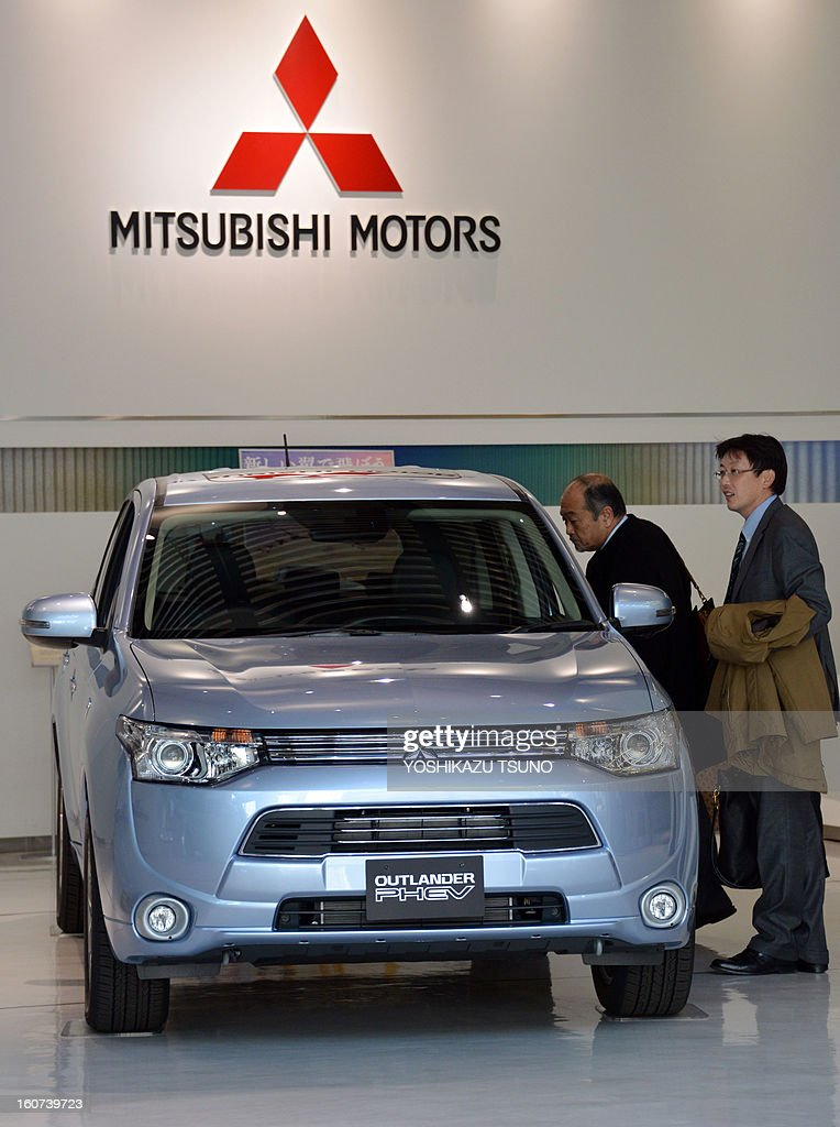 Customers check Mitsubishi Motors' new plug-in hybrid SUV 'Outlander PHEV' at the company's showroom in Tokyo on February 5, 2013. Mitsubishi Motors said its group net profit in the nine months April to December rose 27.3 percent from a year earlier to 17.34 billion yen due to cost-cutting efforts. AFP PHOTO / Yoshikazu TSUNO