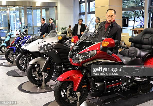 Customers check motorcycles of Japanese auto giant Honda Motor at the company's showroom in Tokyo on January 30 2015 Honda slashed its fullyear net...
