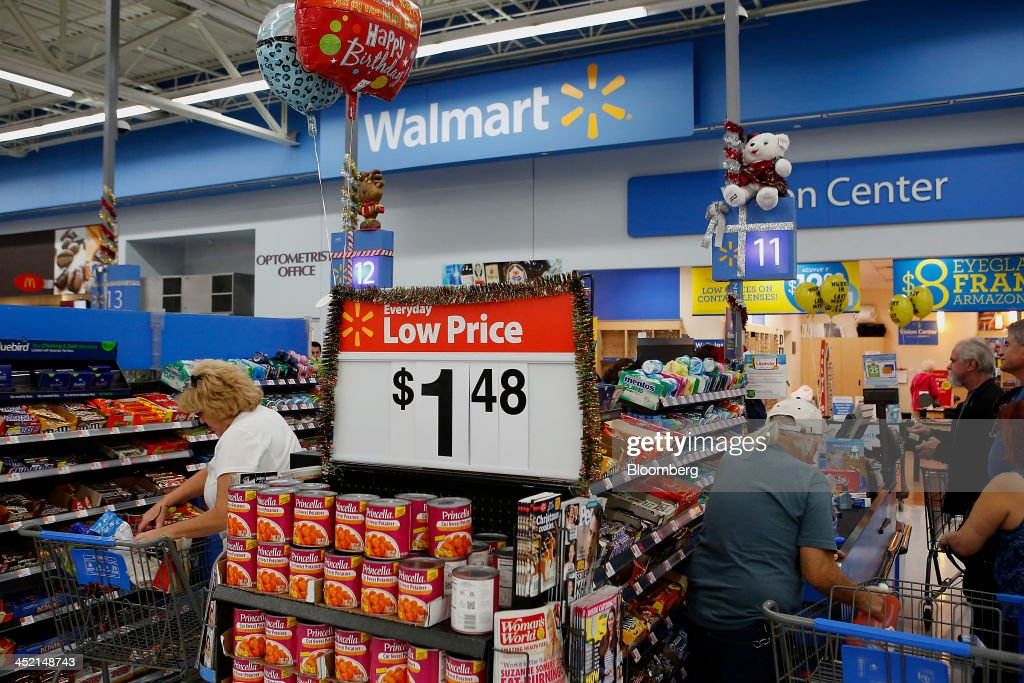 Customers check out at a Wal-Mart Stores Inc. location ahead of Black Friday in Los Angeles, California, U.S., on Tuesday, Nov. 26, 2013. Wal-Mart Stores Inc. said Doug McMillon, head of its international business, will replace Mike Duke as chief executive officer when he retires as the world's largest retailer struggles to ignite growth at home and abroad. Photographer: Patrick T. Fallon/Bloomberg via Getty Images