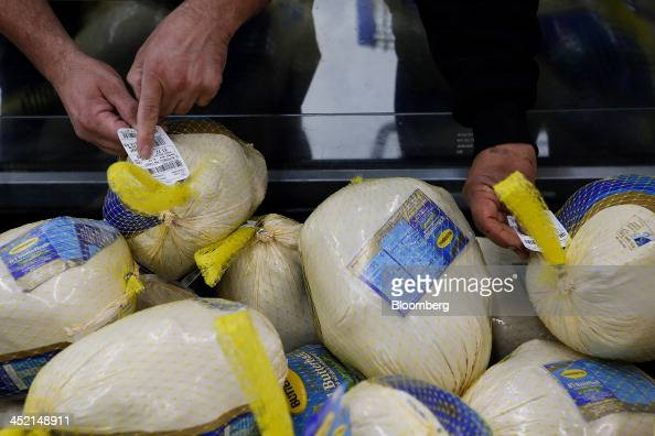 Customers check the price tag on a Butterball frozen turkey on sale at a WalMart Stores Inc location ahead of Black Friday in Los Angeles California...