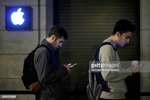 Customers check their mobile phones as they queue at Puerta del Sol Apple Store before its opening the day the company launches their Iphone 7 and 7...