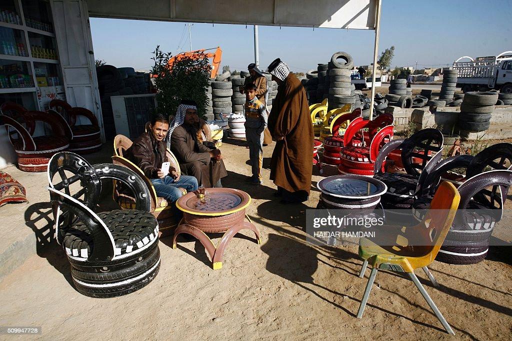 Customers checks the chairs at Abu Haidar's tire repair shop, where he transforms unused tires into furniture, in the Diwaniya village, east of the holy Iraqi city of Najaf, on February 13, 2016. / AFP / HAIDAR HAMDANI