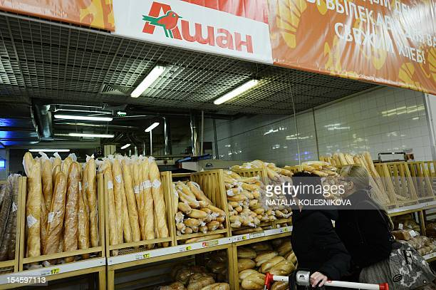 Customers choose bread in an Auchan Hypermarket in Moscow on October 22 2012 The French retail giant established in 1961 entered the Russian market...
