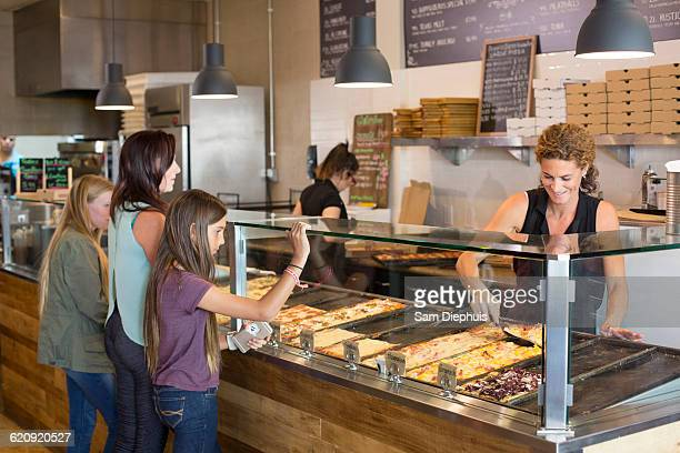 Customers choosing pizza in cafe