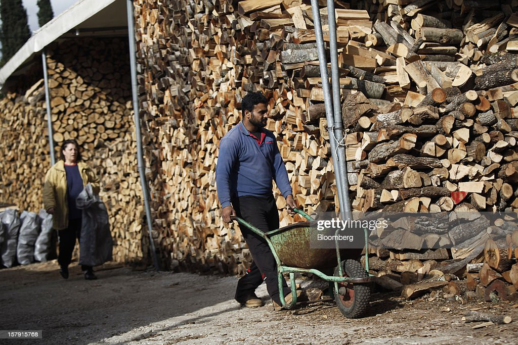Customers collect wood logs to use as heating fuel from a firewood supply store in Athens, Greece, on Friday, Dec. 7, 2012. Greece, the epicenter of Europe's debt crisis since revealing a bloated spending gap in late 2009, has faced regular demands to get a firmer grip on the budget or risk being forced out of the euro. Photographer: Kostas Tsironis/Bloomberg via Getty Images