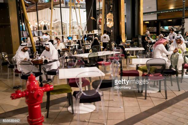 Customers consume food and drink on a cafe terrace in Avenues shopping mall in Kuwait City Kuwait on Sunday Aug 13 2017 Kuwait will issue a tender to...