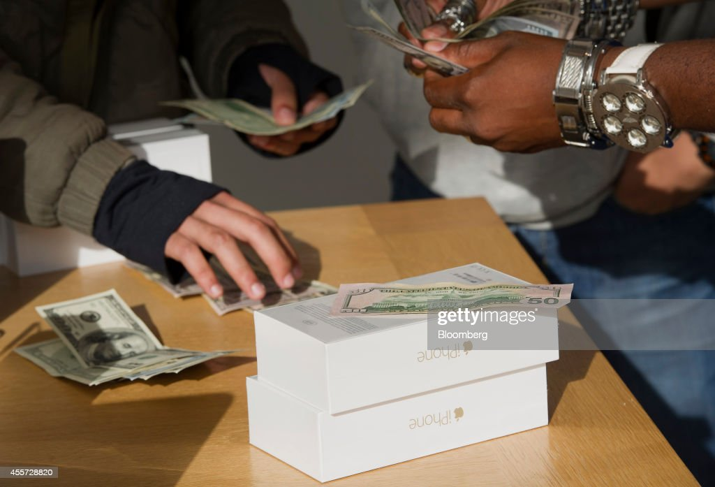 Customers count money while purchasing iPhone 6 smartphones during the sales launch at the Apple Inc. store in Palo Alto, California, U.S., on Friday, Sept. 19, 2014. Apple Inc.'s stores attracted long lines of shoppers for the debut of the latest iPhones, indicating healthy demand for the bigger-screen smartphones. The larger iPhone 6 Plus is already selling out at some stores across the U.S. Photographer: David Paul Morris/Bloomberg via Getty Images