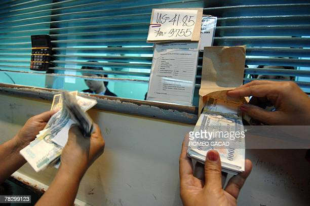 Customers count Philippine peso at a moneychanger in Manila as the local currency hit a fresh seven and a half year high of 4185 pesos against the...