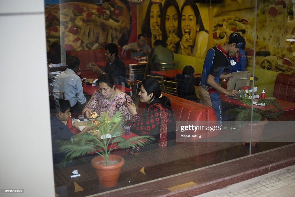 Customers dine inside a Domino's Pizza outlet operated by Jubilant Foodworks Ltd. at Connaught Place in New Delhi, India, on Saturday, Feb. 23, 2013. Finance Minister Palaniappan Chidambaram, who will present his annual budget to parliament on Feb. 28, will seek to narrow the shortfall to 4.8 percent of gross domestic product in the year starting April, from this year's goal of 5.3 percent, according to a Bloomberg survey of analysts and investors. Photographer: Brent Lewin/Bloomberg via Getty Images