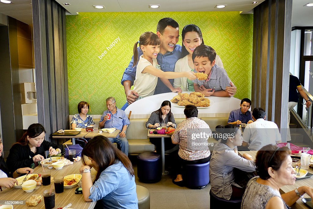 Customers dine inside a Jollibee Foods Corp. restaurant in Quezon City, Metro Manila, the Philippines, on Monday, July 28, 2014. Jollibee, which outsells McDonald's Corp. in the Philippines, plans to double earnings in five years as it accelerates its expansion in China and seeks an acquisition in the U.S. Photographer: Veejay Villafranca/Bloomberg via Getty Images