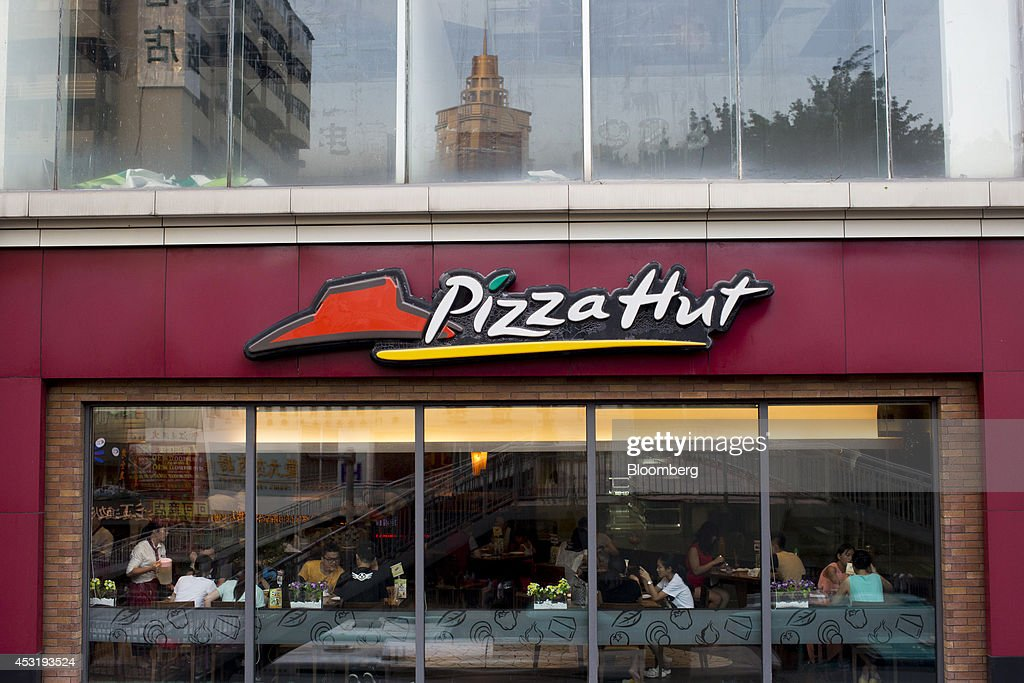 Customers dine inside a Pizza Hut restaurant, operated by Yum! Brands Inc., in the Luohu district of Shenzhen, China, on Monday, Aug. 4, 2014. Yum, owner of Pizza Hut and KFC, said its China team is trying to regain customers after a supply chain scare has recently hurt results. Photographer: Brent Lewin/Bloomberg via Getty Images
