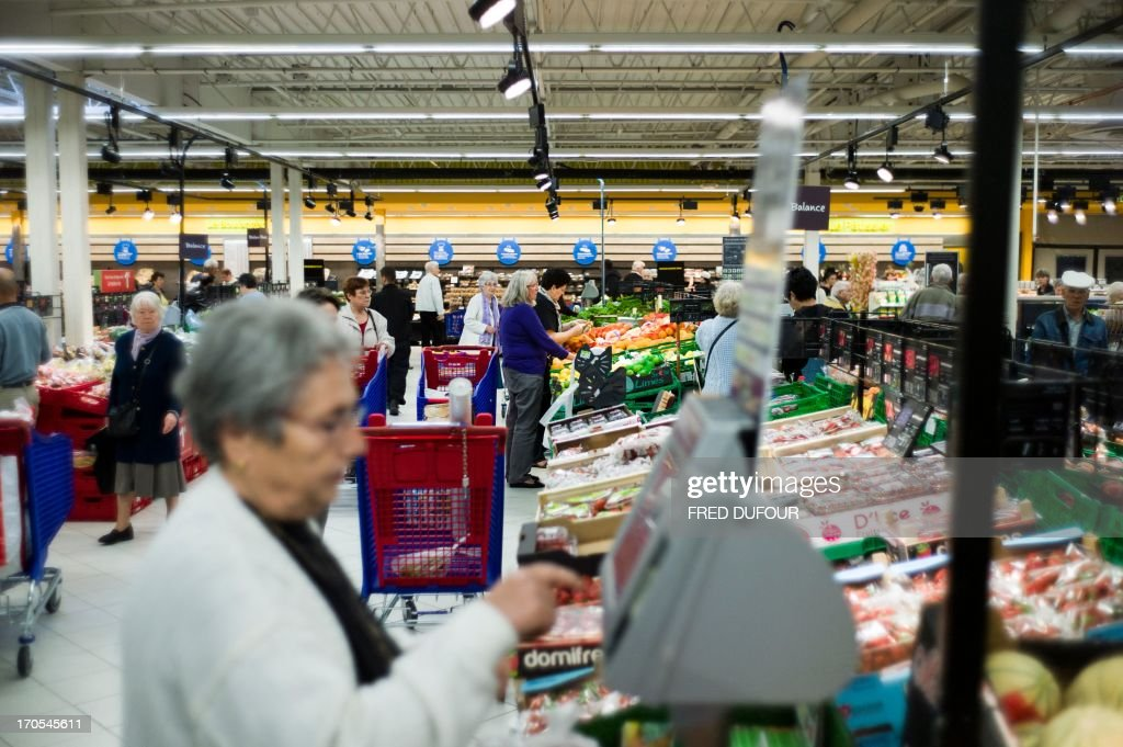 Customers do their shopping at the fruits and vegetables section in a Carrefour supermarket, on June 14, 2013 in Sainte-Geneviève-des-Bois, outside Paris. Installed in Sainte-Geneviève-des-Bois since fifty years, on June 15, 1963, this supermarket is the first of French giant retailer Carrefour group, but also the first in France.