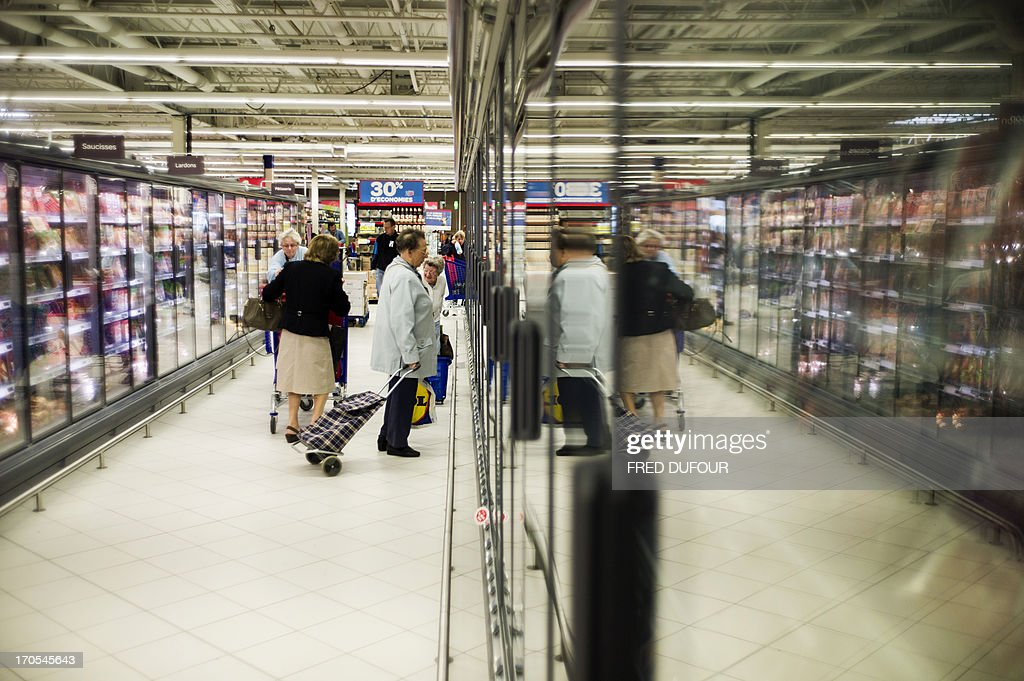 Customers do their shopping in a Carrefour supermarket, on June 14, 2013 in Sainte-Geneviève-des-Bois, outside Paris. Installed in Sainte-Geneviève-des-Bois since fifty years, on June 15, 1963, this supermarket is the first of French giant retailer Carrefour group, but also the first in France. AFP PHOTO / FRED DUFOUR