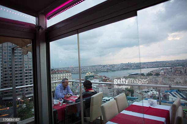 Customers eat an evening meal at a rooftop restaurant overlooking the skyline of Istanbul Turkey on Thursday June 13 2013 The law forbids the sale of...