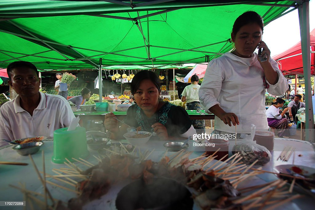 Customers eat at a cooked-food stall at a market in Naypyidaw, Myanmar, on Friday, June 7, 2013. President Thein Sein has allowed more political freedom and loosened economic controls since coming to power two years ago, prompting the U.S. and other nations to ease sanctions. Photographer: Dario Pignatelli/Bloomberg via Getty Images