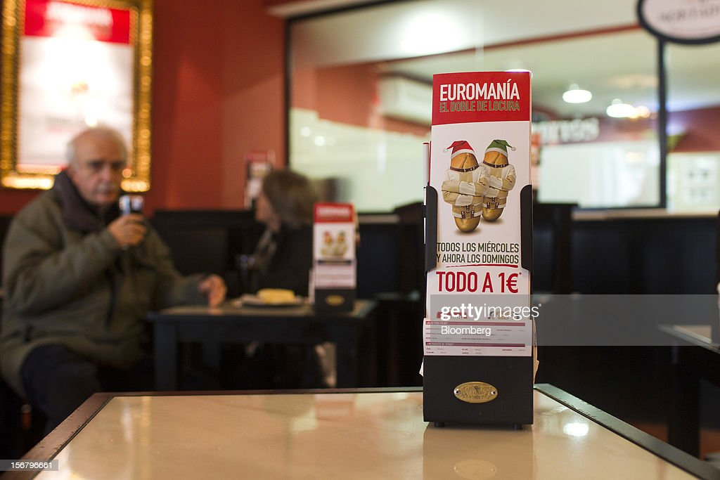 Customers eat at tables near promotional cards advertising one euro menus as part of 'Euromania' Wednesdays in a 100 Montaditos restaurant in Madrid, Spain, on Wednesday, Nov. 21, 2012. The Madrid-based chain in January opened its first U.S. restaurant in Miami and aims to have eight outlets in Florida by next March. Photographer: Angel Navarrete/Bloomberg via Getty Images