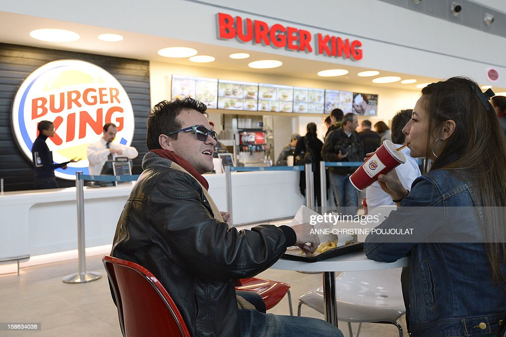 Customers eat at the Burger King fast food restaurant in Marseille's airport, in Marignane, southern France, on December 22, 2012. Marignane's Burger King is the first shop of the brand to open in France after 15 years of absence and marks the return of the famous Whopper burger in the country.