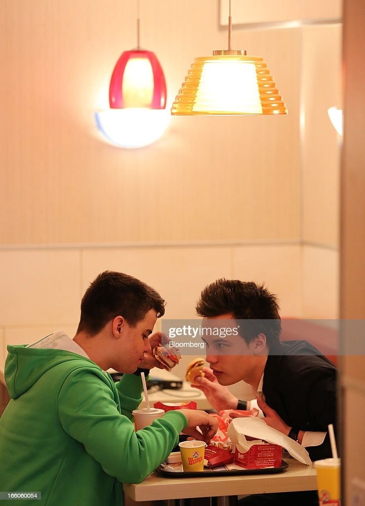 Customers eat hamburger meals at a table inside a Wendy's fast food restaurant in Moscow, Russia, on Friday, April 5, 2013. McDonald's, which virtually created the market for burgers and fries in the country and convinced Russians it's OK to eat with their hands, must fend off a growing challenge from rivals Burger King Worldwide Inc., Subway Restaurants, Yum! Brands Inc. and Wendy's Co. Photographer: Andrey Rudakov/Bloomberg via Getty Images