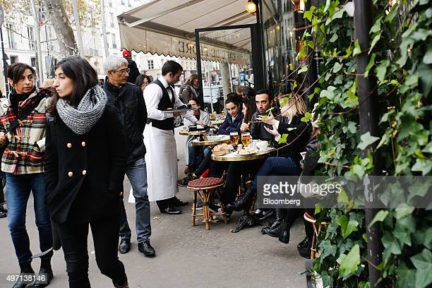 Customers eat lunch outside a cafe in Paris France on Saturday Nov 14 2015 French President Francois Hollande blamed Islamic State militants for...