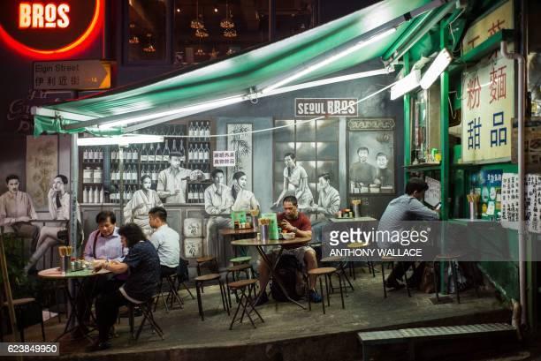 TOPSHOT Customers eat noodles at a street food stall or 'dai pai dong' in Cantonese in Hong Kong on November 17 2016 Dai pai dongs have dwindled to...