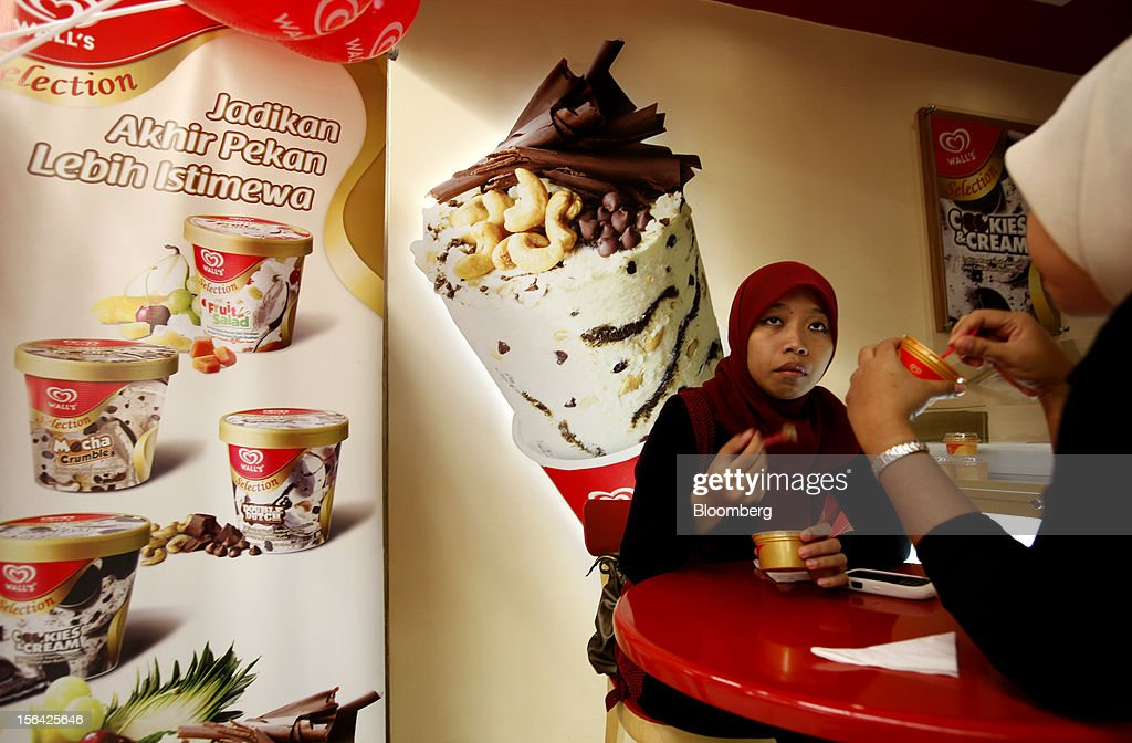 Customers eat Unilever NV's Wall's brand ice cream at a Lotte Shopping Co. Lotte Mart outlet at Kuningan City Mall in Jakarta, Indonesia, on Wednesday, Nov. 14, 2012. Unilever has accelerated the rollout of shampoos and deodorants to emerging markets such as Indonesia and China to offset slowing growth in developed markets, where higher price tags have deterred consumers. Photographer: Dadang Tri/Bloomberg via Getty Images